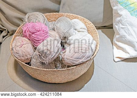 Multicolored Skeins Of Yarn In A Wicker Basket For Knitting And Needlework.
