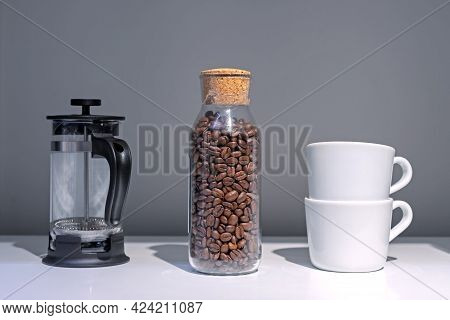 Roasted Coffe Grains In A Glass Jar, French Press And Two White Coffe Cups.