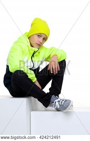 Cute Stylish Boy Posing On Staircase. Preteen Boy Wearing Sports Tracksuit With Sweatshirt, Pants An
