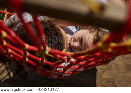 A View Through The Hammock Net Of A Little Girl Kissing Her Mother, Lying Next To Her And Relaxing O