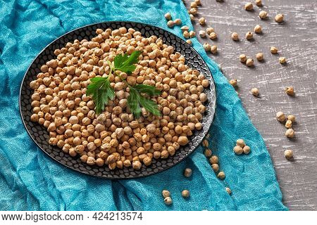 Raw Dry Chickpea Beans On A Black Plate Over Turquoise Cloth. Raw Ingredient For Hummus And Healthy