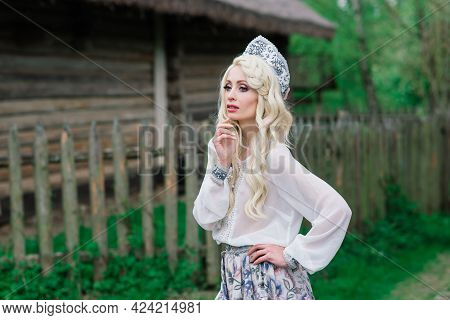 A Young Female Of Slavic Appearance With Crown, Kokoshnik On The Midsummer, Village, Homestead