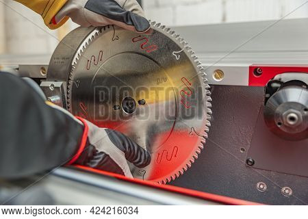 Saw Disk Circle Install. The Craftsman Installs The Circular Saw Blade On The Woodworking Machine. C
