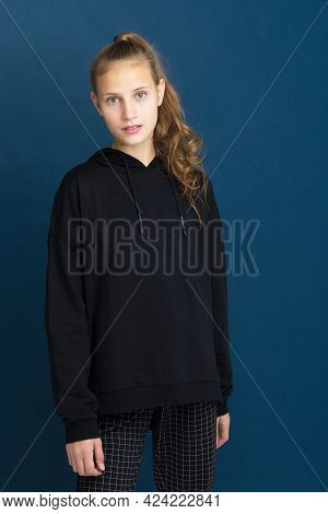 Pretty Teenage Girl In Black Stylish Clothes. Portrait Of Adorable Girl With Ponytail Dressed Sweats