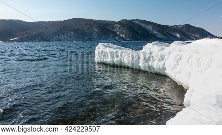 The Icy And Snow-covered Promontory Juts Out Into The Ice-free River. Icicles Over Water. Stones Are