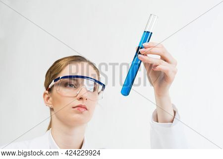 Laboratory Analysis And Testing. Beautiful Woman Scientist In Protective Goggles Holding Test Tube W