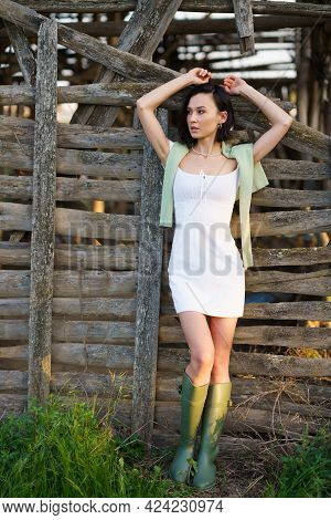 Asian Woman, Posing Near A Tobacco Drying Shed, Wearing A White Dress And Green Wellies.