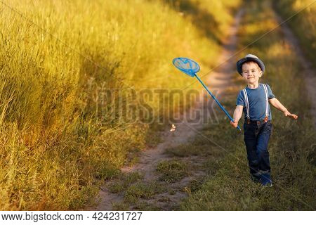 Little Boy Catches Butterflies With Net On The Meadow