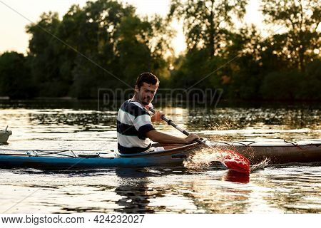 Enthusiastic Young Caucasian Guy Having Fun While Boating On A Lake Surrounded By Nature. Kayaking,
