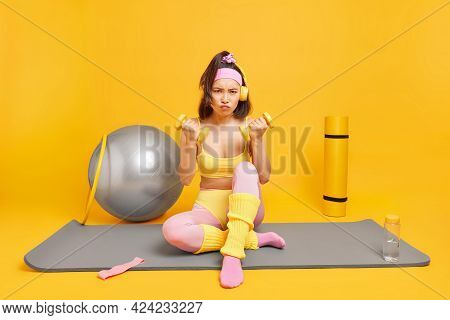 Full Length Shot Of Grumpy Asian Woman Sits On Fitness Mat Holds Dumbbells Dressed In Activewear Use