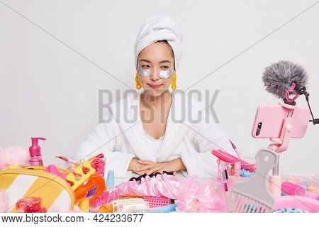 Serious Woman Vlogger Wears White Bathrobe Towel Wrapped Over Head Yellow Earrings Applies Silver Pa