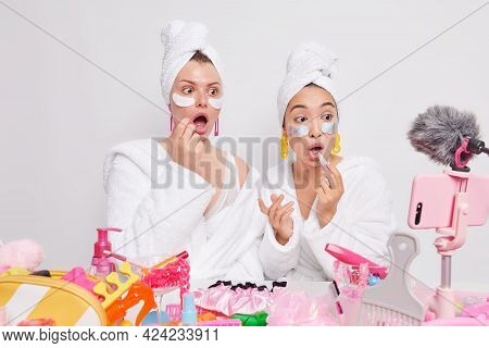 Stunned Diverse Women Stare At Camera Apply Lipstick And Beauty Patches Keep Mouth Opened Dressed In