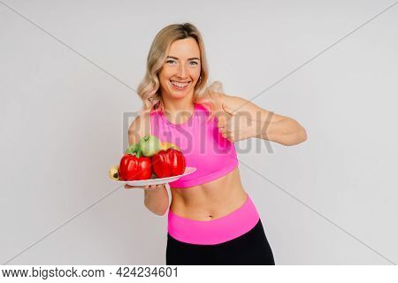 Studio Shot Of Young Fitness Woman In Sports Clothing Holding Green Apple, Fruits, Vegetables.