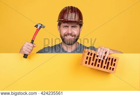 Happy Mature Man Bricklayer Behind Yellow Paper For Copy Space Hold Hammer And Brick, May 1.