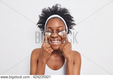 Portrait Of Cheerful Dark Skinned Woman Smiles Broadly Points At Beauty Patches Closes Eyes Has Perf
