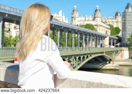 Portrait Of A Blonde Woman In The City. Bir Hakeim Bridge And Historic Building Deliberately Blurred