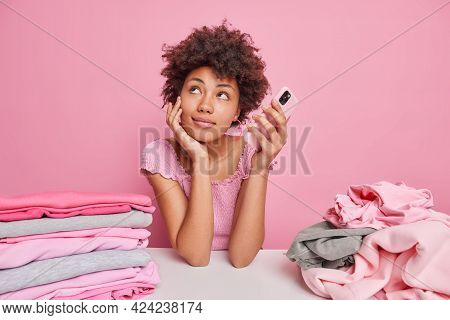 Dreamy Afro American Woman Folds Clean Clothes After Laundry Leans At White Table Holds Mobile Phone