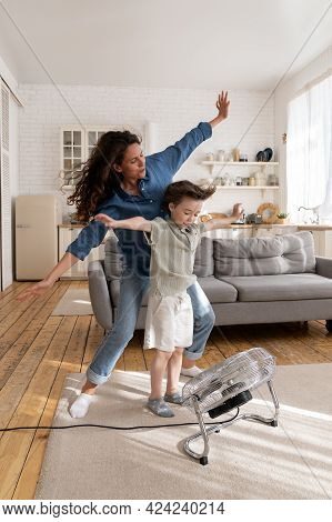 Carefree Mom And Kid Have Fun At Home Play With Wind From Ventilator, Indoor Air Fan Cheering And Bo