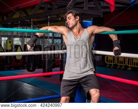 Young Male Boxer Resting Against Boxe Ring Ropes