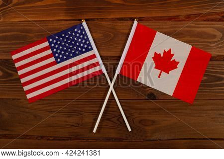Flag Of Usa And Flag Of Canada Crossed With Each Other. Usa Vs Canada. The Image Illustrates The Rel