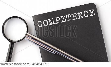 Competence - Business Concept, Magnifier With White Text Message On Black Notebook