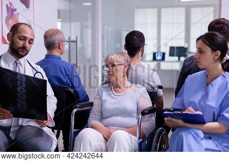 Doctor With Stethoscope Communicating To Disabled Senior Woman Radiography In Wheelchair Test Result