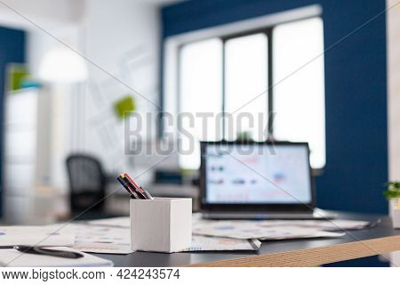 Corporate Moderl Office With Laptop On Desk Showing Finaicial Charts. Brainstorm Area In Business Ce