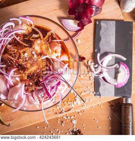 Cooking Asian-style Chicken. Chopped Chicken Breast In Bowl With Hot Sauce And Chopped Onion With In