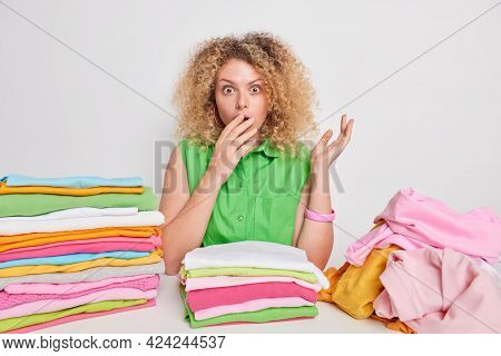 Impressed Young Woman With Shocked Expression Covers Mouth Surrounded By Folded Clothes And Pile Of