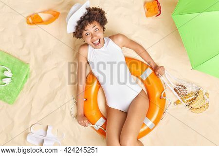 Surprised Positive Afro American Woman Looks Gladfully At Camera Dressed In White Bikini And Sunhat