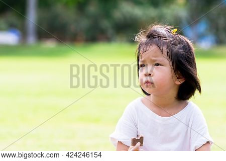 Asian Child Eating Chocolate Wafers On Natural Green Laws Background. Cute Girl Holding Sweetmeat On