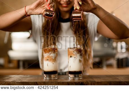 Process Of Making Cold Coffee Cocktail. Woman Carefully Pours Espresso From Cups Into Glasses
