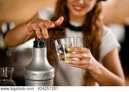 Womans Hand Pressing On Dispenser While Squeezing Delicious Topping Into Transparent Glass