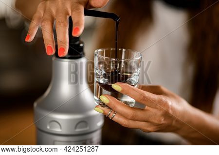 Close-up Of Womans Hand Pressing Dispenser While Squeezing Chocolate Topping Into Transparent Glass