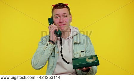 Cheerful Teen Boy Secretary In Denim Jacket Talking On Wired Vintage Telephone Of 80s, Says Hey You