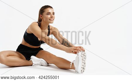 Sport And Workout. Smiling Jogger, Female Athlete Doing Stretching Exercises Indoors, Isolated White