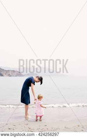 Mom Leaned Over To The Little Girl While Standing In The Water On The Beach