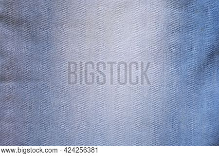 Denim Fabric Close Up. Light Blue Jeans Top View. Textile Background, Texture Of Jeans With Frayed.