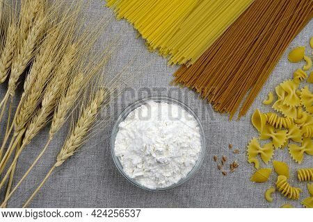 Flour, Pasta, Spaghetti And Wheat Spikelets On Gray Linen Fabric Top View. Durum Wheat Pasta. Produc