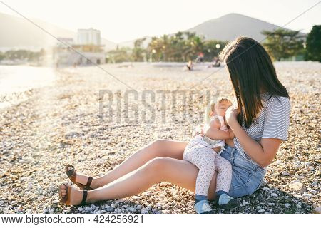 Mom Sits On A Pebble Beach And Breastfeeds A Little Girl By The Sea