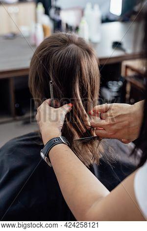 Woman Getting A New Haircut. Female Hairstylist Cutting Her Long Black Hair With Scissors In Hair Sa