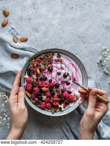 Hands Holding A Bowl Of Natural Yogurt With Oat Granola, Frozen Raspberries, Blueberries, Nuts And S