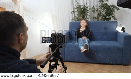 Kid Video Blogger. Videographer Shoots A Video Blog In A Studio With A Little Girl For An Online Pla