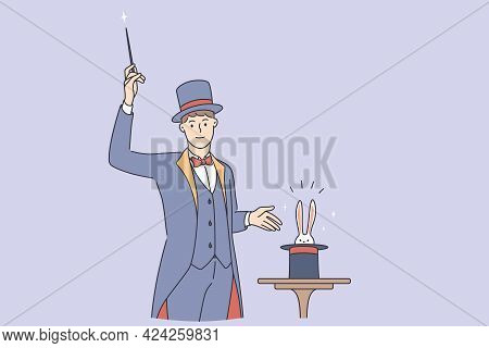 Magician Making Trick During Work Concept. Young Smiling Man Magician Wearing Traditional Costume St