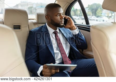 Wealthy Black Manager Sitting In Car And Using Digital Tablet