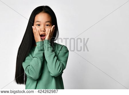Discouraged Surprised Asian Girl Ten Years Old In Green Clothes Touching Cheeks With Both Hands Stan