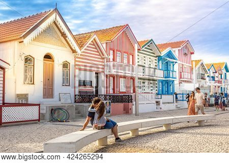 Tourists Relax On The Street With Typical Striped Fishing Houses Costa Nova, Aveiro, Portugal. Costa
