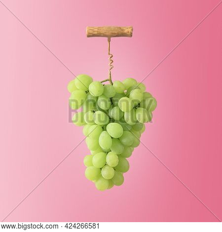 The Creative Concept Of Winemaking. A Bunch Of Grapes With A Wine Corkscrew On A Pink Background.