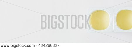 Two Open Plastic Cups With Yellow Fruit Yogurt On A White Background. View From Above. Free Space Fo