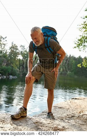 Tired Middle Aged Caucasian Man With Aching Knee Hiking Alone In Summer Nature, Vertical Shot. Hikin